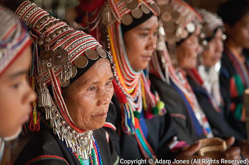 Akha hilltribe women wearing ornate headress performing traditional Akha dance, northern Thailand near Chiang Rai.