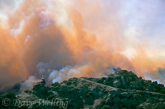870000369 a los angeles county fire fighting helicopter performs an aerial drop of  retardant on a burning hillside in the path of the topanga fire in the hills above the san fernando valley in southern california