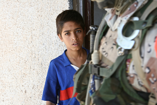 A boy stares from the doorway of his home as U.S. and Iraqi soldiers search it for weapons and suspected insurgents in Baqubah, Iraq,  during a U.S.-led offensive to clear the city of al Qaida and other fighters. June 25, 2007. DREW BROWN/STARS AND STRIPES
