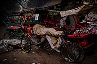 OLD DELHI, INDIA, JANUARY 11, 2016: A rickshaw driver sleeps on his rickshaw adjacent to a sleep market, from where he rented a blanket on January 11, 2016 in Old Delhi, India. <br /> Daniel Berehulak for The New York Times