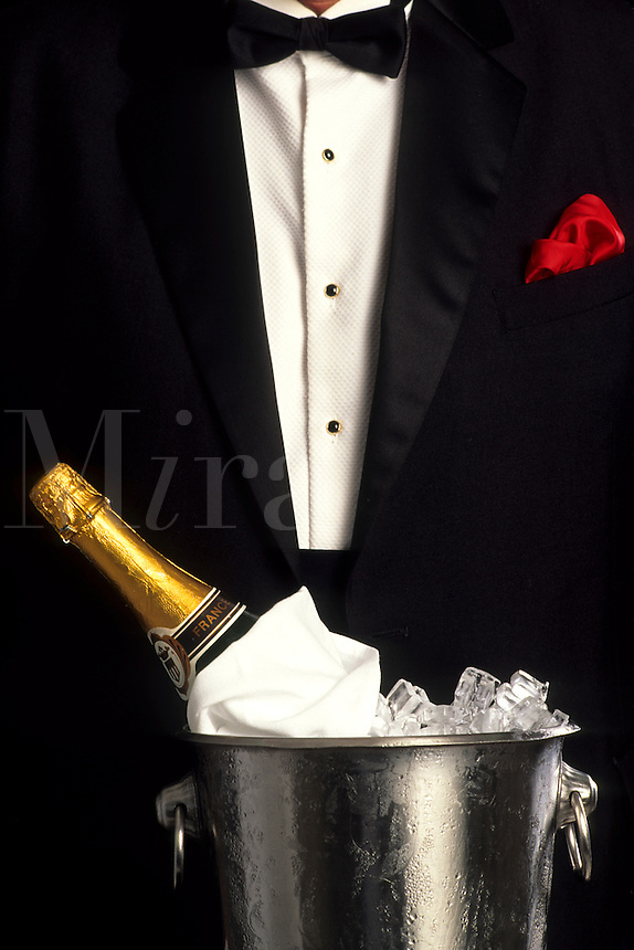 Waiter in tuxedo with ice bucket and champagne to celebrate occasion party
