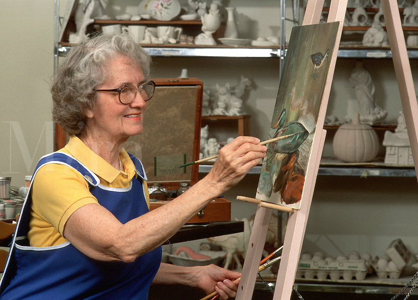 A smiling senior woman painting on an easel.