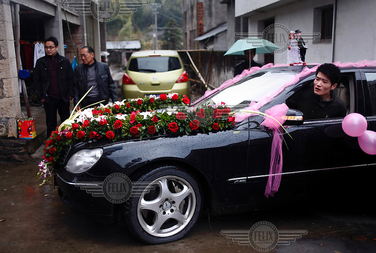 The driver of a Mercedes car, decorated for a wedding, watches out of the window as he meanouves with care along a narrow village street. The car is taking the groom to collect the bride from her village.