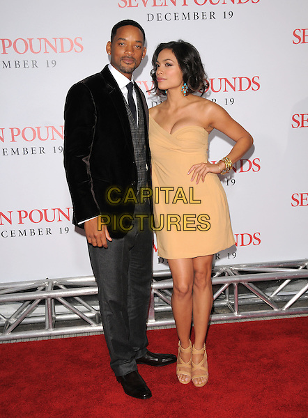 "WILL SMITH & ROSARIO DAWSON.L.A. Premiere of ""Seven Pounds"" held at The Mann Village Theatre in Westwood, California, USA. .December 16th, 2008.full length black jacket grey gray waistcoat check checked yellow cream orange dress off the shoulder one hand on hip sandals heels shoes .CAP/DVS.©Debbie VanStory/Capital Pictures."