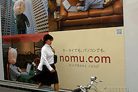 A woman walks past an advertisement of Nomu.com, a consumer property information service and part of the massive Nomura company, advertise their services on a billboard in Tokyo, Japan..13 May 2006