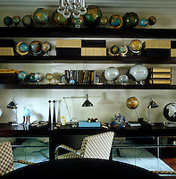 A collection of globes is displayed on open shelving in the study