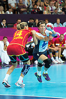 28 JUL 2012 - LONDON, GBR - Marie Gerbron (GBR) of Great Britain (right, in white, blue and red) finds her path to goal blocked by Maja Savic (MNE) of Montenegro (left, in red and gold) during the women's London 2012 Olympic Games Preliminary round handball match at The Copper Box in the Olympic Park, in Stratford, London, Great Britain (PHOTO (C) 2012 NIGEL FARROW)