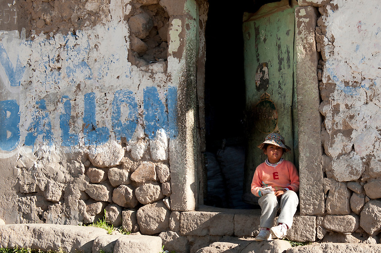 A child sits in doorway of her home in Colca Valley, Peru.  Like most cities, those in Peru and Bolivia have loads of graffiti on the wall.  However, unlike in the U.S., most graffiti there is explicitly political.
