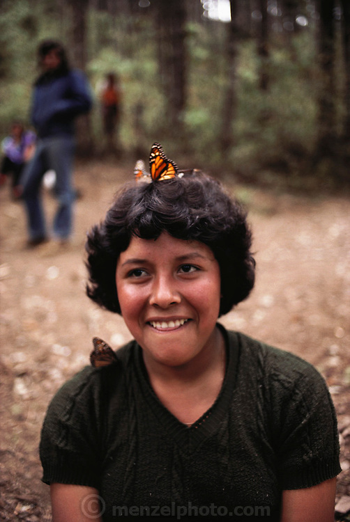 A teenage girl visitor with Monarch butterflies on her head and shoulder. Rosario, Mexico.