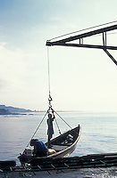 Boy standing in a fishing boat being lowered into the Pacific Ocean from the town pier in La Libertad, El Salvador