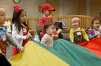 NWA Democrat-Gazette/DAVID GOTTSCHALK Juniper Sciulli (center), 16 months, participates in a parachute activity Wednesday, February 28, 2018 during the Rattle & Rhyme Toddler Time event that the Springdale Public Library. The theme on Wednesday was bugs and the children listen and sang bug themed songs, listened to bug themed books and made a lady bug craft.