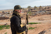 KURDISTAN, NORTHERN IRAQ, Dokuk.<br /> Qalubna Ma'Kum Feature:<br /> Qalubna Ma'kum (meaning &quot;Our hearts are With You&quot;) are a group of foreign volunteer fighters who have joined up with the Peshmerga in Kurdistan to help with the battle against Daesh, also known as ISIS. <br /> <br /> Pictured: Joe Pollard of Qalubna Ma'kum stands in front of town which had been flattened by coalition airstrikes two weeks before.