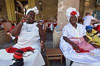 Havana, Cuba. La Habana Vieja (Old Habana). Santeria priestesses posing with cigars for tourists at Plaza de la Catedral.
