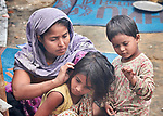 A Rohingya woman, having just crossed the border from Myanmar, checks her daughter's hair for lice as they to complete registration in the Kutupalong Refugee Camp near Cox's Bazar, Bangladesh.<br /> <br /> More than 600,000 Rohingya refugees have fled government-sanctioned violence in Myanmar for safety in this and other camps in Bangladesh.