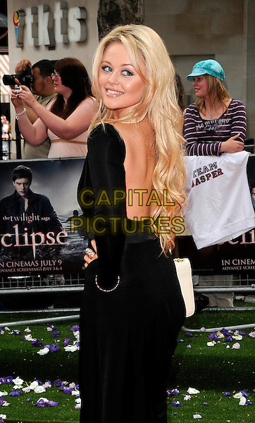 "EMILY ATACK.UK Gala Premiere of ""The Twilight Saga: Eclipse"" at the Odeon Leicester Square, London, England, UK..July 1st 2010.half length dress bag black hand on hip long sleeves white purse looking over shoulder backless.CAP/CAN.©Can Nguyen/Capital Pictures."