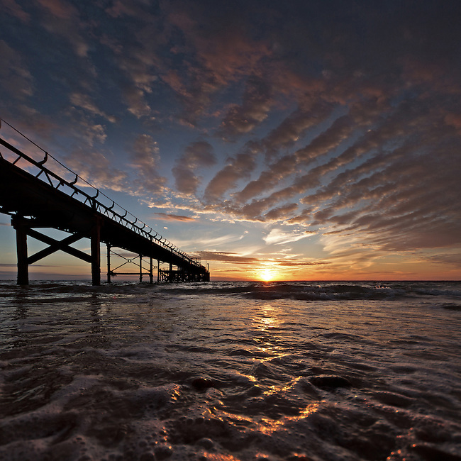 Altocumulus clouds catching the last light as the sun goes down one summers evening at Totland Pier on the Isle of Wight.<br />
