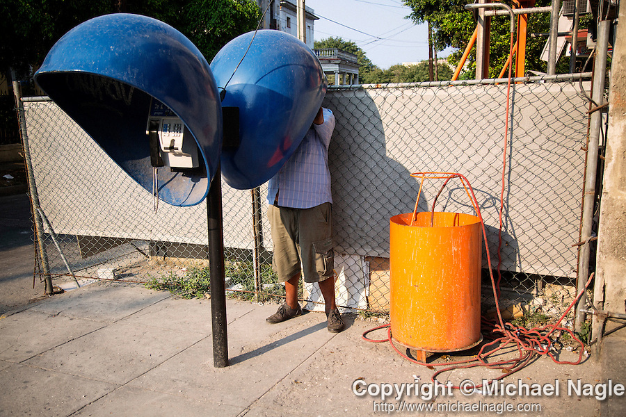 HAVANA, CUBA -- MARCH 25, 2015:   A man uses a payphone in Havana, Cuba on March 25, 2015. Photograph by Michael Nagle