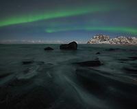 Northern Lights over rocky coastline at Uttakleiv beach, Vestvågøy, Lofoten Islands, Norway
