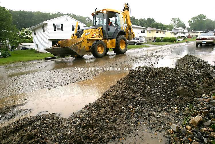 WATERBURY, CT, 03 June 2006- 060306BZ02- Waterbury Street Department worker Donald Dapont uses a backhoe to clean debris from Tedesco Drive in Waterbury Saturday afternoon.  Heavy rains throughout the area flooded streets  and caused severe damage.<br /> Jamison C. Bazinet Republican-American