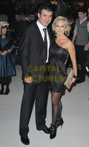 """JOE CALZAGHE & KRISTINA RIHANOFF.The World Premiere of Disney's """"A Christmas Carol"""", Odeon Leicester Square, London, England..November 3rd 2009.full length dress black one shoulder tie white shirt couple polka dot tights ankle boots beige clutch bag .CAP/CAN.©Can Nguyen/Capital Pictures."""