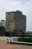 Female student with the Central library in the background, Universidad Nacional Autonoma de Mexico or UNAM in Mexico City. The library is covered in murals by Juan O'Gorman. This university campus is a UNESCO World Heritage site.