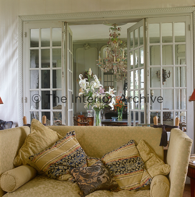 A sofa upholstered in a gold colour fabric with cushions stands in a sitting room. Behind is a glazed panel with a pari of French doors that open into a reception room.