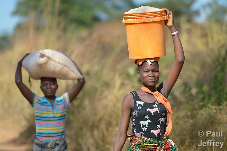 Women carry heavy containers on their heads in Edundu, Malawi. They and other farmers in the village have benefited from intercropping and crop rotation practices they learned from the Malawi Farmer-to-Farmer Agro-Ecology project of the Ekwendeni Mission Hospital AIDS Program, a program of the Livingstonia Synod of the Church of Central Africa Presbyterian.