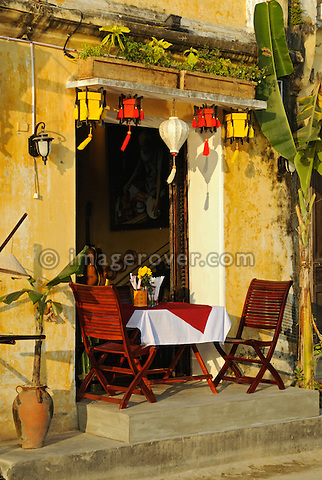 Asia, Vietnam, Hoi An. Hoi An old quarter. Tastefully arranged table at the restaurant Hoa Vang on the Bach Dang river promenade. The historic buildings, attractive tube houses, and decorated community halls have 1999 earned Hoi An's old quarter the status of a UNESCO World Heritage Site. To protect the old quarter's character stringent conversation laws prohibit alterations to buildings, as well as the presence of cars on the roads.