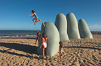 Josefina Barbero, 8, leaps from the pinky finger of a giant sculpture of a hand protruding from the sand of the playa brava beach in Punta del Este, Uruguay. The venerable South American beach resort is having a rennaisance. (Kevin Moloney for the New York Times)