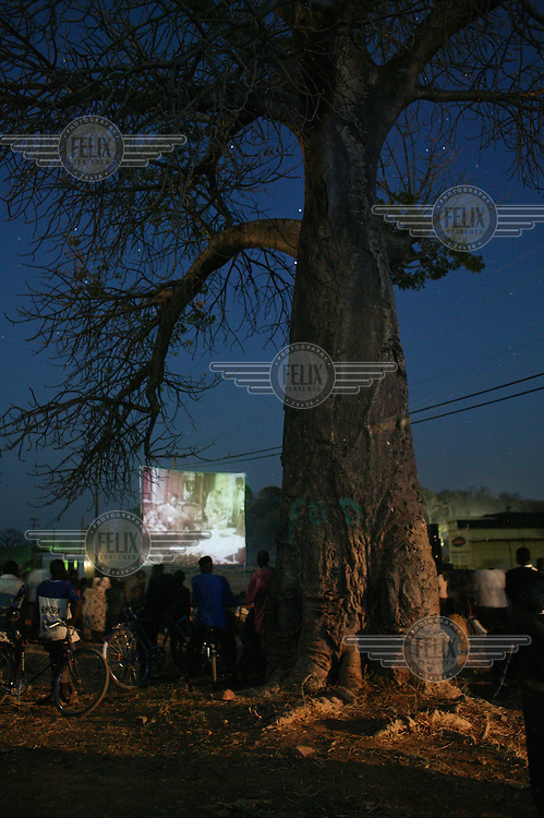 Travelling film show in a village without power on the banks of Lake Kariba. The film show is a soap opera punctuted by live actors advertising washing powder. The travelling show brings its own generator as the village has no mains power.