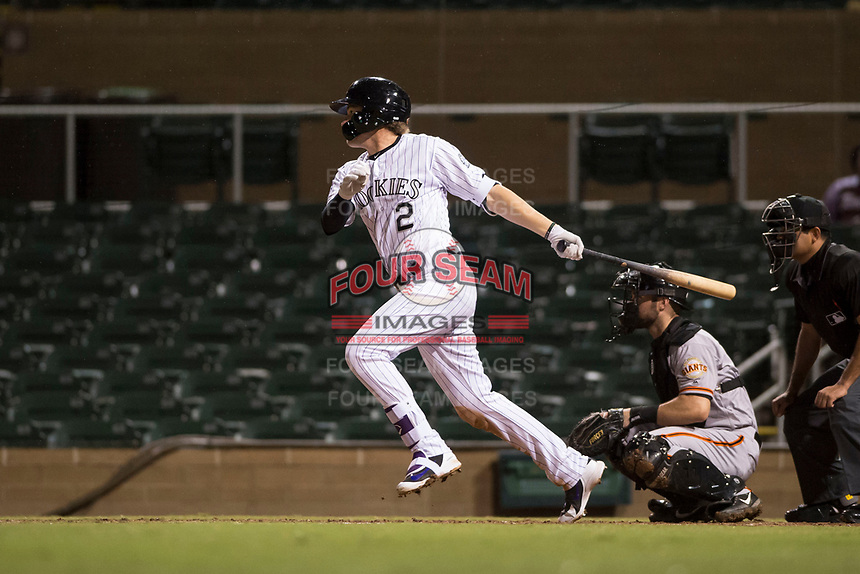 Salt River Rafters first baseman Tyler Nevin (2), of the Colorado Rockies organization, follows through on his swing in front of catcher Matt Winn (16) and home plate umpire Nestor Ceja during an Arizona Fall League game against the Scottsdale Scorpions at Salt River Fields at Talking Stick on October 11, 2018 in Scottsdale, Arizona. Salt River defeated Scottsdale 7-6. (Zachary Lucy/Four Seam Images)