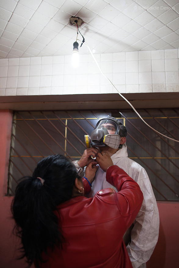 "Donovan's assistant helps Donovan get ready to begin a forensic cleaning in Iztacalco, Mexico on October 16, 2015. The decomposed body of a man in his 60s was found in his bedroom a number of days after he died of a heart attack – although the deceased's own family members were unsure exactly how long he had been there. The victim's family remarked that the police had made unfounded insinuations against them, and had sought bribes. As a result they found Donovan's discretion and professionalism to be a welcome contrast. Donovan Tavera, 43, is the director of ""Limpieza Forense México"", the country's first and so far the only government-accredited forensic cleaning company. Since 2000, Tavera, a self-taught forensic technician, and his family have offered services to clean up homicides, unattended death, suicides, the homes of compulsive hoarders and houses destroyed by fire or flooding. Despite rising violence that has left 70,000 people dead and 23,000 disappeared since 2006, Mexico has only one certified forensic cleaner. As a consequence, the biological hazards associated with crime scenes are going unchecked all around the country. Photo by Bénédicte Desrus"