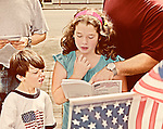 Girl reading Declaration of Independence at July 4th Celebration, with father pointing to part in book, and young boy looking on. Merrick, New York, July 4, 2011. =Vintage tint treatment.=