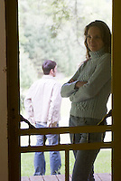 Woman leaning screen door, man in background