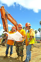 Local construction workers wearing hard hats discuss plans for a project on Ford Island, Pearl Harbor, a military historical site.