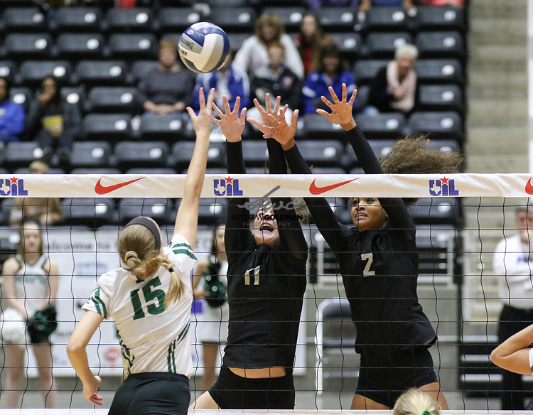 Rouse Raiders seniors Mackenzie Huntley (11) and McKenzie Wells (12) go up to attempt to block an attack from Prosper Eagles senior Hope Gramly (15) during the Class 5A high school volleyball state final between Rouse High School and Prosper High School at Curtis Culwell Center in Garland, Texas, on November 18, 2017. Prosper won the match in five sets, (25-18, 21-25, 18-25, 25, 23, 16-14) to win the 5A state championship.