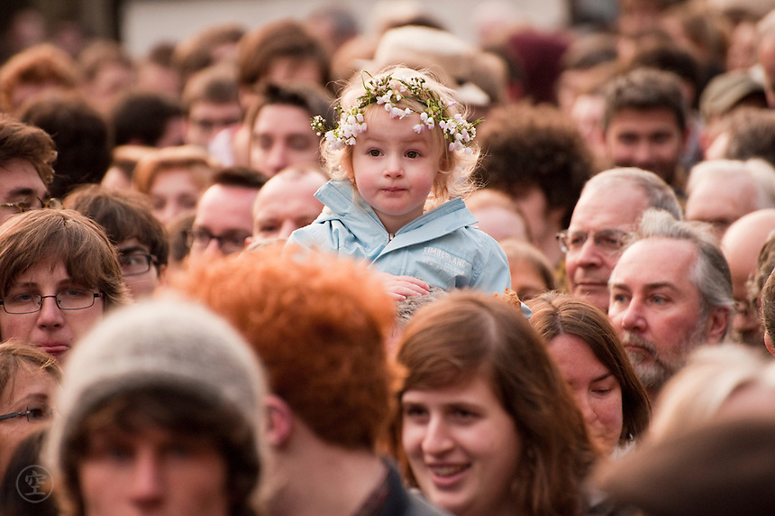 A young child, crowned with white lily flowers, rides on a parent's shoulders to see above the crowds on May Morning in Oxford.