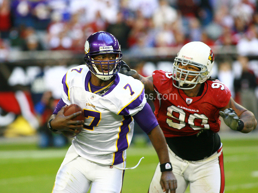 Dec 07, 2008; Glendale, AZ, USA; Minnesota Vikings quarterback Tarvaris Jackson (7) is chased from behind by Arizona Cardinals defensive tackle Darnell Dockett (90) in the third quarter of a game at University of Phoenix Stadium.  The Vikings won the game 35-14.