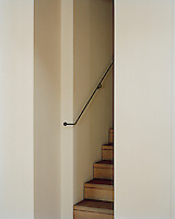 A discreet staircase of uncarpeted wood with a slender metal banister links the upper and lower floors of the apartment