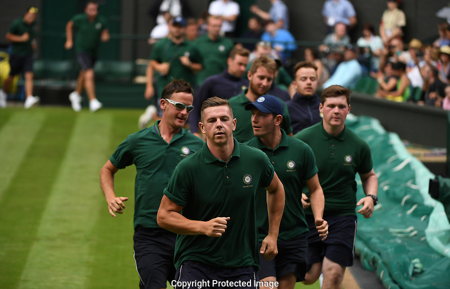 Grounds staff run to cover centre court as it starts to rain