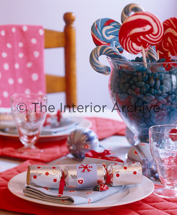 Details of a handmade Christmas cracker on a red and blue themed table
