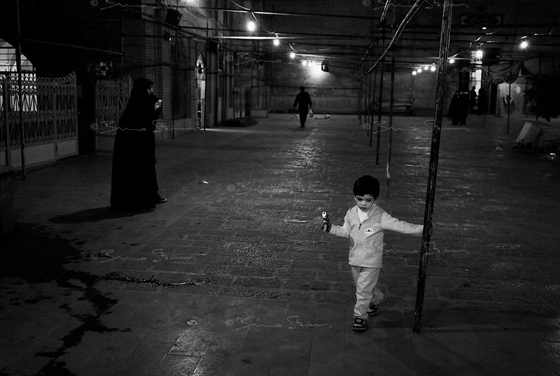 Teheran, Iran, October 2, 2007.Thousands of worshippers mourn all night long the death of their Imam Ali, one of the holiest figures for the Shia Muslems. Morteza, 4, plays with his new toy gun in the Masjed Jameh mosque courtyard while waiting patiently for the long prayers to start.