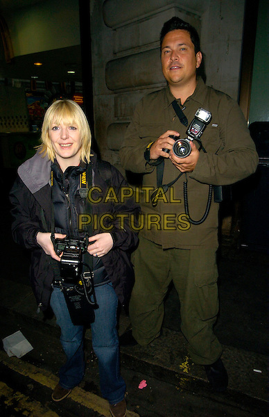 YVETTE FIELDING & DOM JOLY.The Marine Connection annual charity night, Chinawhite bar & nightclub, London, England..April 25th, 2007.full length black coat jeans denim camera cameras paparazzi green shirt combat trousers  .CAP/CAN.©Can Nguyen/Capital Pictures