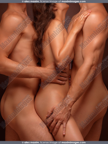 Erotic photo of a naked young woman and two men