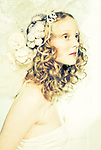 Young woman with blonde hair wearing a head garland and white dress