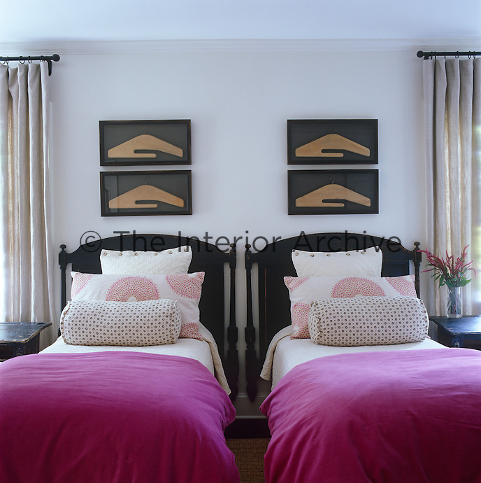 This guest bedroom has been laid out in perfect symmetry with matching bed linen on the twin beds and identical prints hanging above them