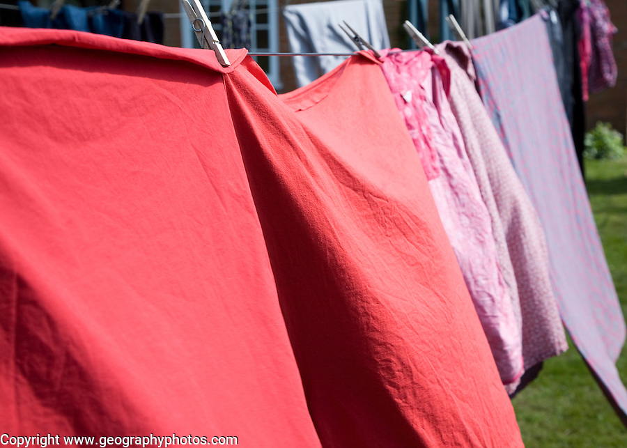 Red pink and purple clothes drying on washing line