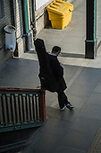 Man with a guiter on his back, train station platform, London.