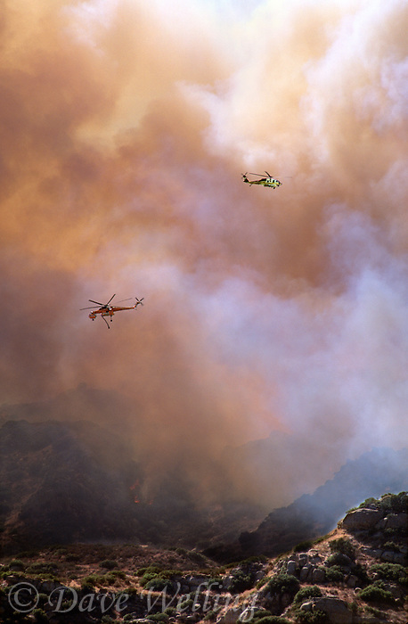 870000392 two los angeles county fire fighting helicopters fly over a burning hillside in the path of the topanga fire in the hills above the san fernando valley in southern california
