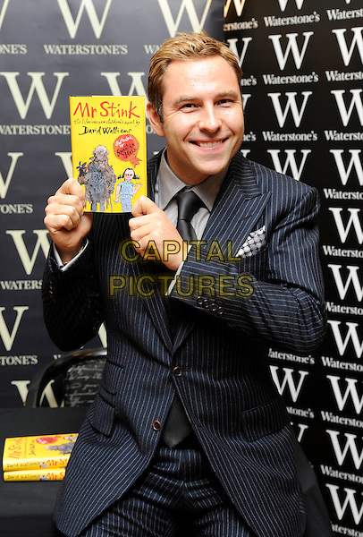 "DAVID WALLIAMS.Book Signing for ""Mr. Stink"" at Waterstone's,  Bluewater Shopping Centre, Greenhithe, Kent, England, UK, .20th November 2009. .half length black pinstripe suit tie grey gray shirt sitting smiling .CAP/FIN.©Steve Finn/Capital Pictures"
